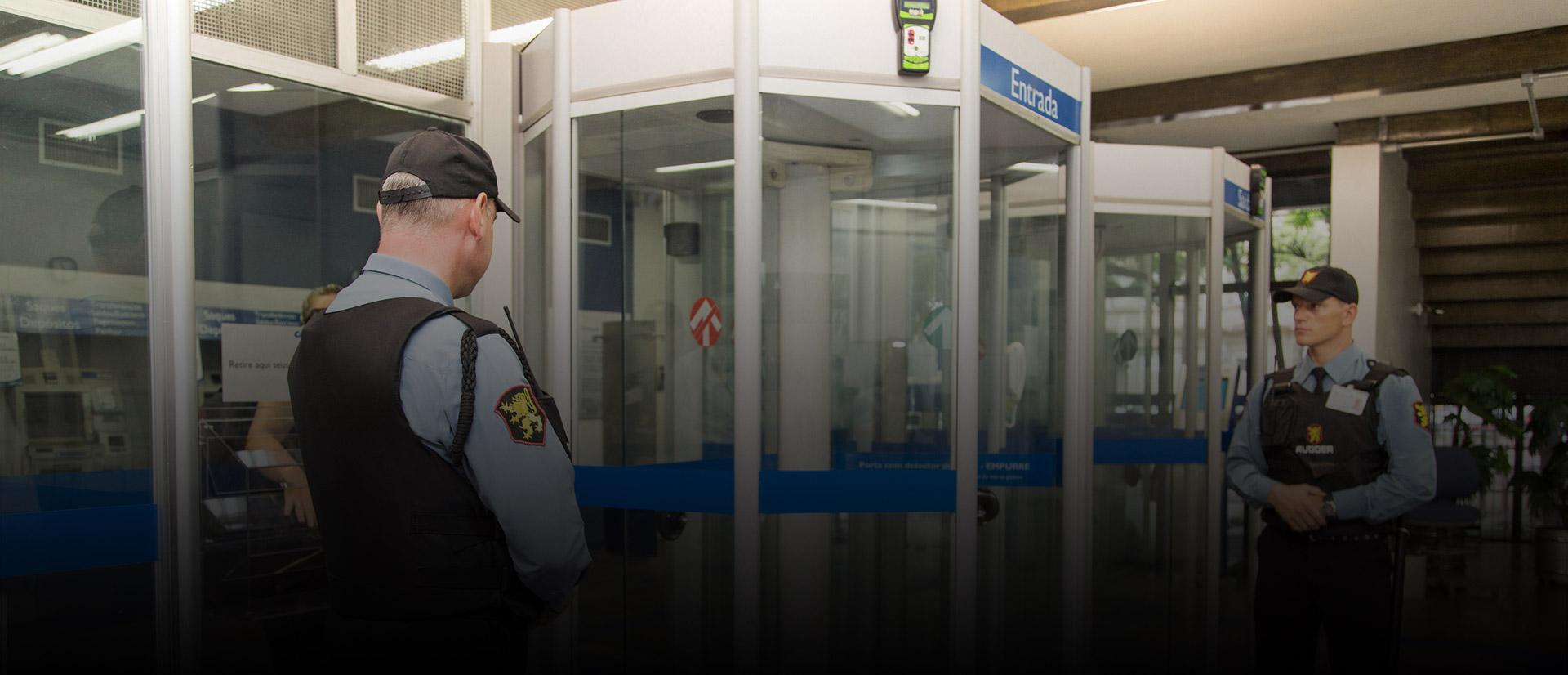 Agentes de segurança em frente à porta-giratória de um banco
